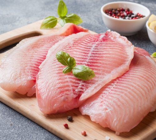 Raw fish fillet of tilapia on a cutting Board with lemon and spices. Dark table,