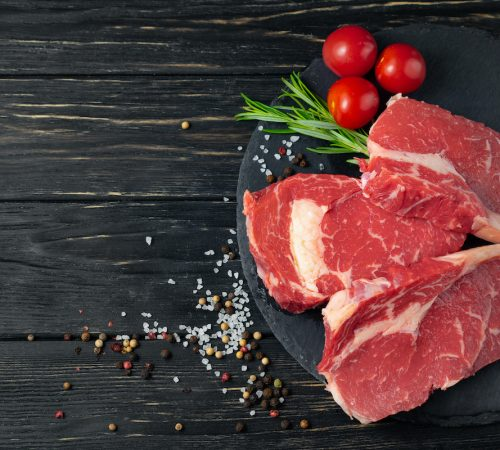 Three pieces of juicy raw beef with rosemary on a stone cutting board on a black wooden table background. Meat for barbecue or grill next to cherry tomatoes sprinkled with pepper and salt seasoning